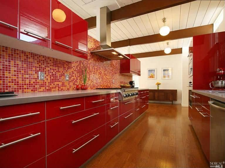 Long red galley kitchen with red and orange tile backsplash and stainless steel appliances all under a white ceiling with large wood beams.
