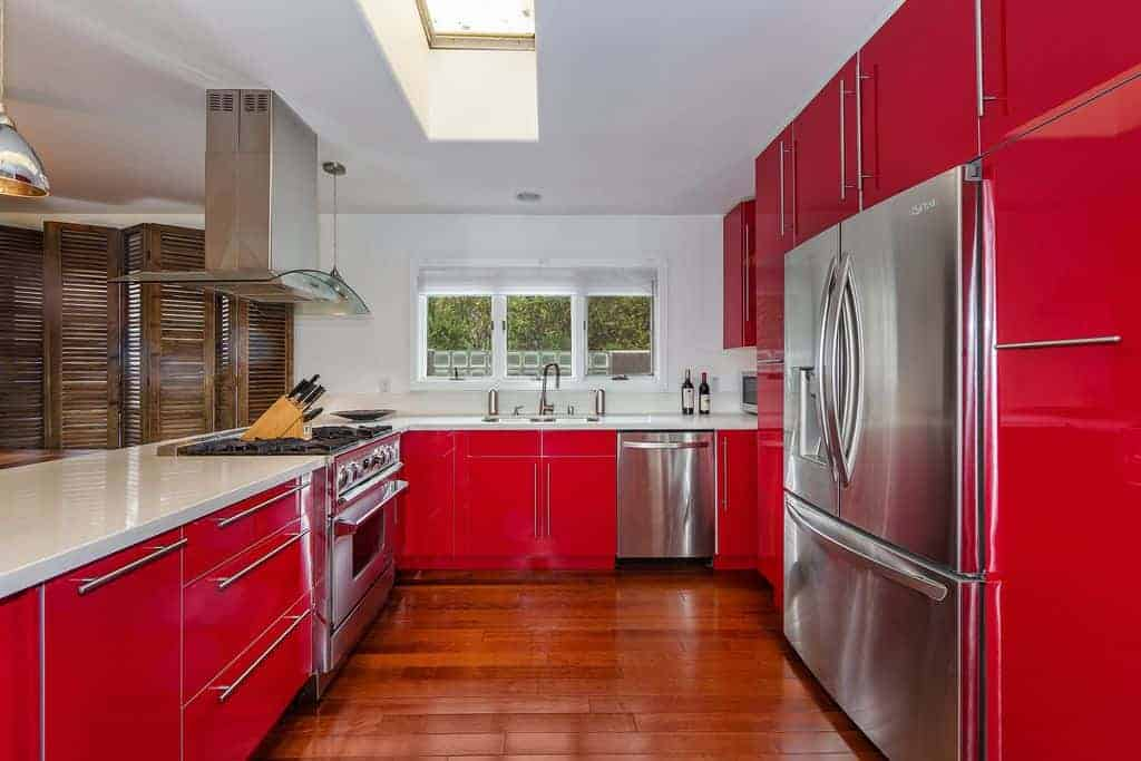 Large U-shaped kitchen with bright red cabinetry and stainless steel appliances with white countertops and white ceiling. I think the reddish wood floor fails to offer sufficient contrast... I think a light wood floor would look better.