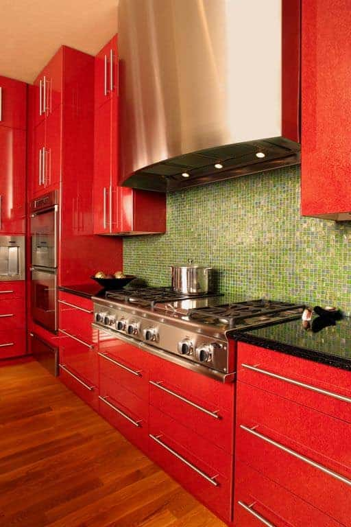 Close-up of bright red kitchen cabinets with chrome hardware. There's a green tile backsplash and a reddish wood floor. I'm not big on the green backsplash, but I do like that partcular hue of red.