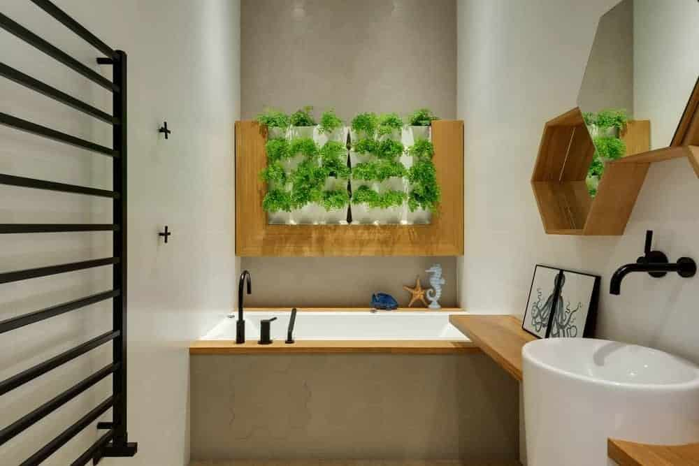 This is a small bathroom complemented by the wooden elements that stand out against the bright walls and pedestal sink. These are then complemented by the vertical garden above the bathtub area.