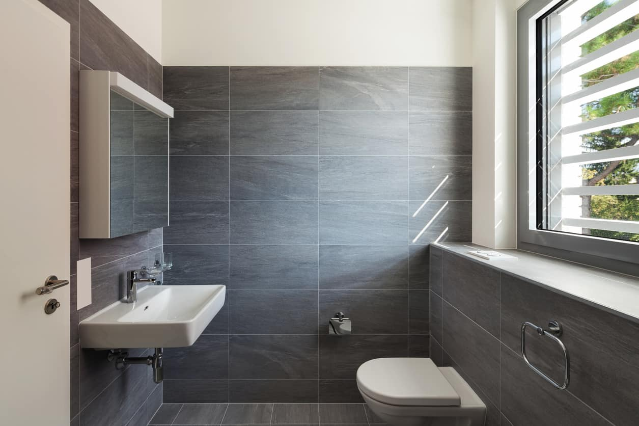 Leveraging a no-frills attitude, the ashen textured graphite walls are gloriously illuminated by a well positioned window that offers natural vistas.