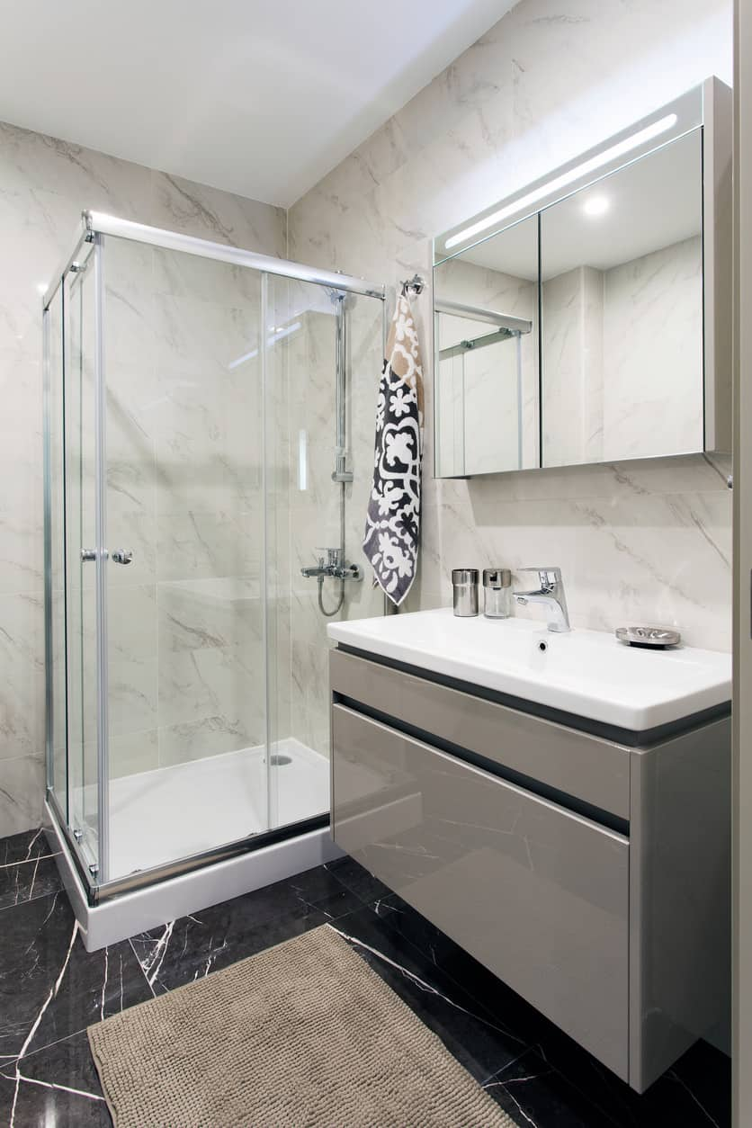 The vanity fixture is astoundingly accentuated with aesthetically appealing lustrous metallic gray finishing. Dark gray floor tiles imbue ebullience to a suave, sleek and clean-looking, lightly-colored interior.