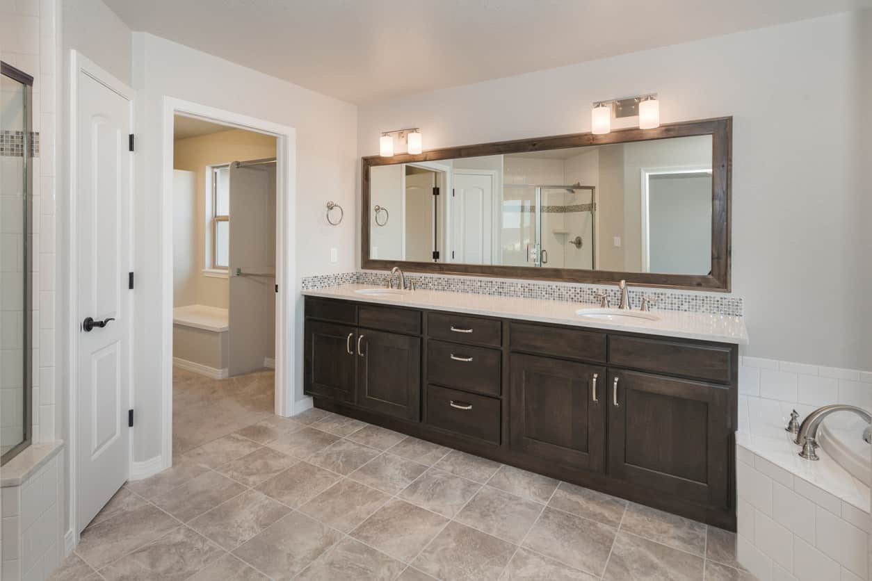 Well-designed layout optimizes floor space through a comfortable bath tucked into a niche. Striated beige tiles and white interior contrasts with ashen gray vanity fixture