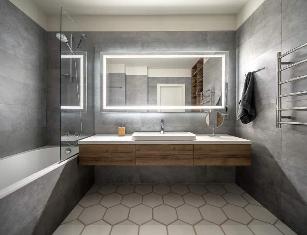 Even under scant lighting the smooth gray tiles look pleasingly refulgent that is blissfully serene to the eye of the beholder. Antique looking fine wood finishing along with smoky ashen gray granite tiles adorning the walls and bath of this interior vouchsafe a veneer of regal luxury.