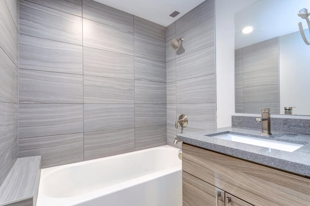 Light gray marble slab lining the basin and bluish gray tiles covering the walls evoke a sense of comfort and modern appeal. A gray slab of marble and light gray tiles exuding slight tinge of blue pleasantly decorate this starkly simple interior.
