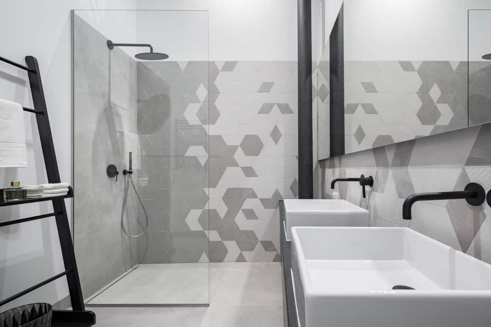 Full-sized mirror imbues symmetric charm to underscore the enigmatic geometry of light gray textured tiles. Geometric artistry is vividly expounded by the lush gray tiles that bedeck the walls of this stunning interior that astounds with jet black faucets, fixtures and showerhead.