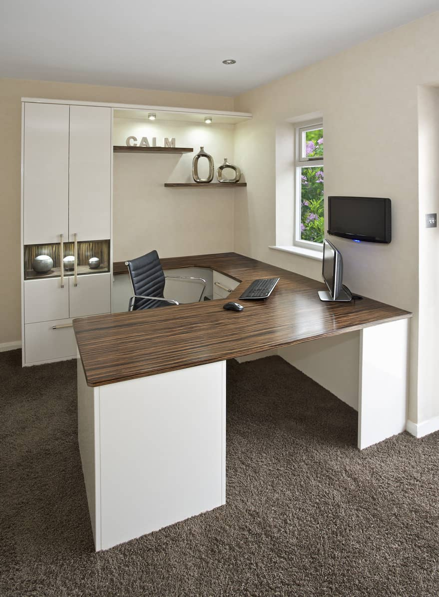 A close-up look at this elegant office desk set on the room's carpet flooring. The walls are just classy, which perfectly fits with the room's style.