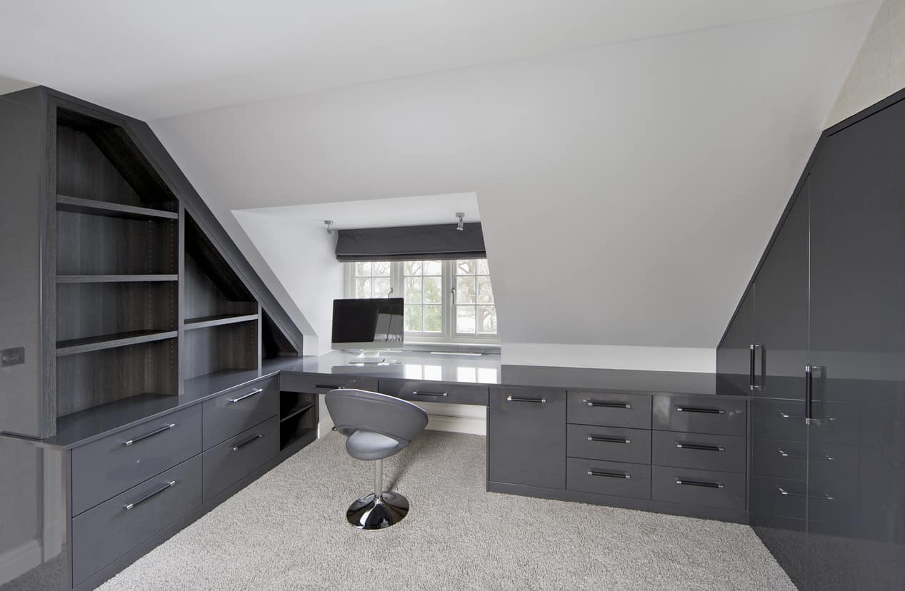 A modish home office with stylish gray cabinetry and built-in desk and chair set on the carpet flooring.