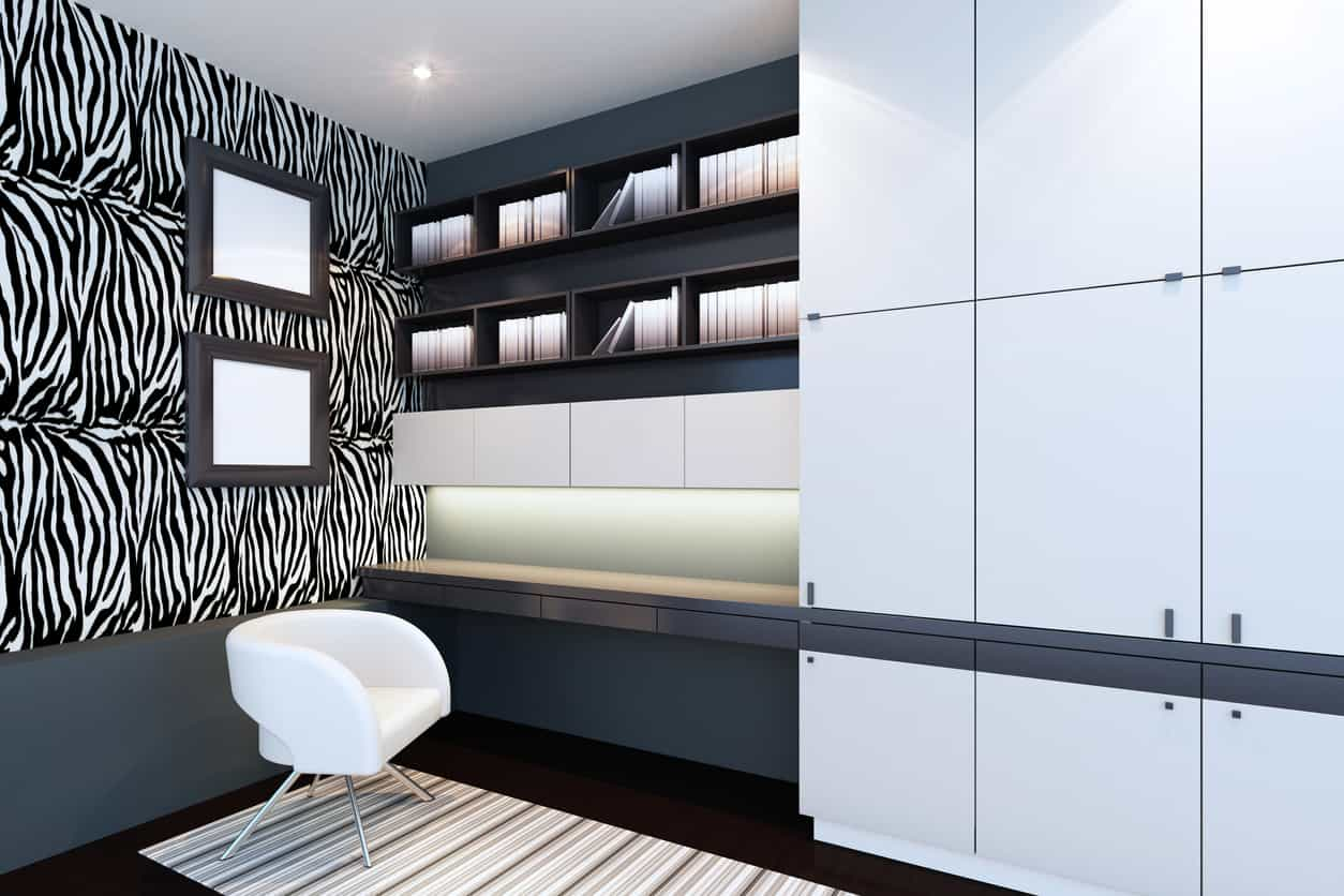 Modern home office with an attractive wall design along with a built-in desk and shelves.