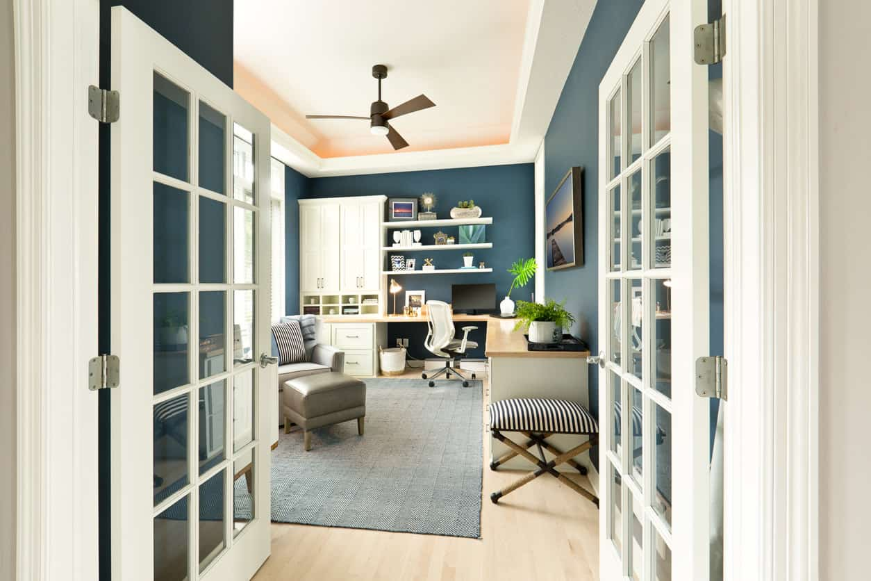This home office features L-shaped office desk surrounded by stylish blue walls. The tray ceiling looks absolutely gorgeous.