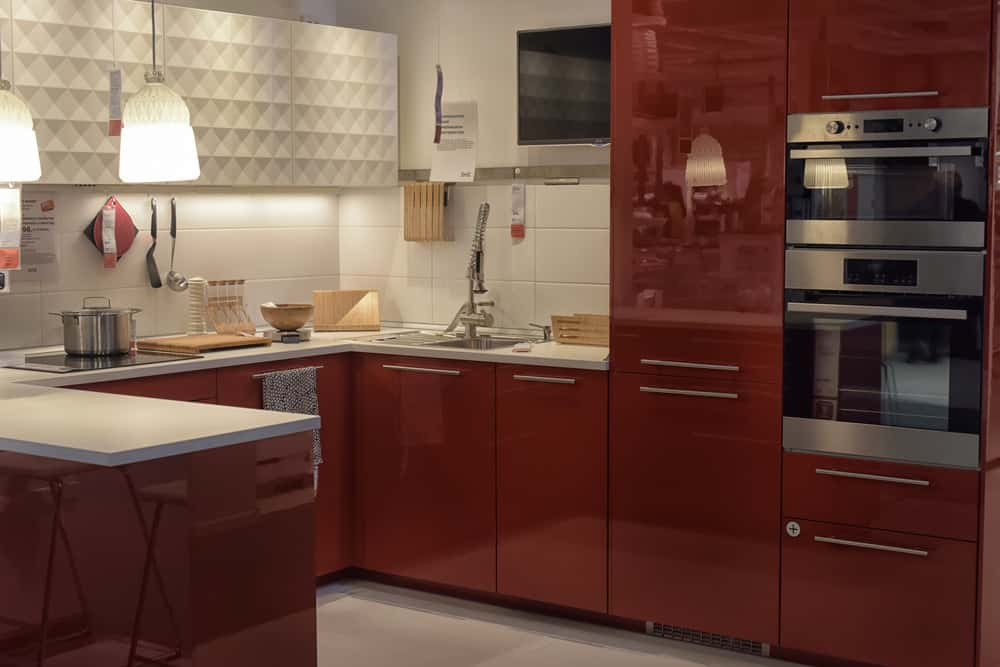 The fixtures in this kitchen mimic the beautiful crimson colors of redwood. The walls and the floors are of soft muted, white and grey shades and the hanging lamps provide plenty of light to brighten up the room.