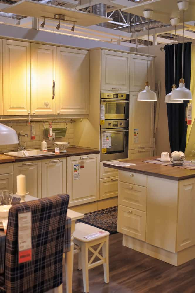 This tiny and cozy kitchen has an extremely welcoming atmosphere. The furniture and fixtures are a soft cream color. The brown tartan armchair next to the kitchen table and the warm, golden glows from the lamps further adds to the homeliness of the kitchen.