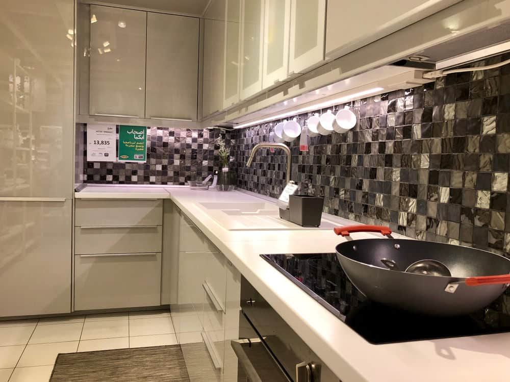 This lovely kitchen offers a juxtaposed effect with its black marble tiling and its pale countertops and fixtures. The black wall tiles provide a dampening effect to the white colors while at the same time their square shape complements the rectangular floor tiles and the sleek lines of the fixtures.
