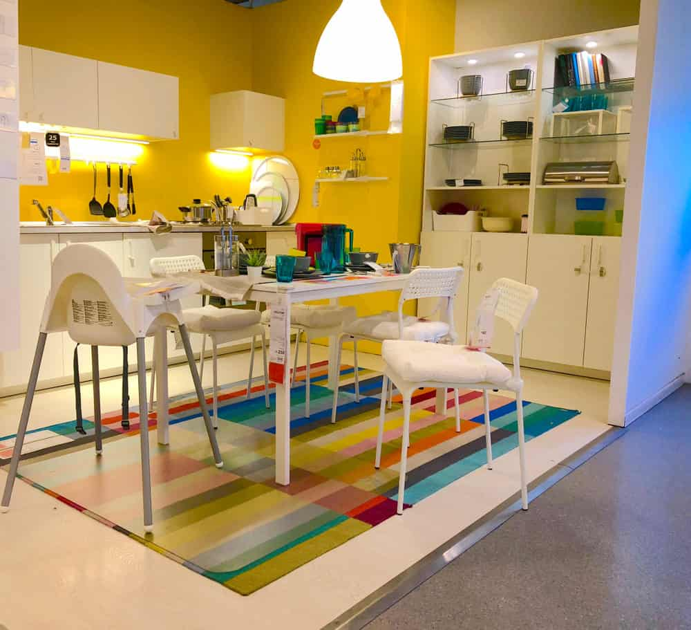 At close glance, you will realize that the fixtures, furniture and floor of this kitchen are completely white — but that's not the first impression you get when you walk into this vibrant room. The center of attention is the rainbow colored rug beneath the table as well as the mango yellow walls. This seems like a fun place for the kiddies.
