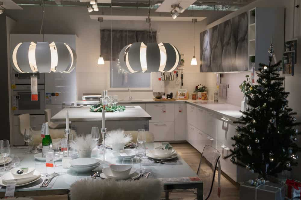 This kitchen has taken inspiration from the white winter season. The chairs are draped in white fur and the same material is displayed on the center of the table. The silver Chinese-lantern styled lamps and the white and grey fixtures further add a cool tint to the room. A Christmas tree with silver baubles stands to one side, perfecting the impression of a snowy night.