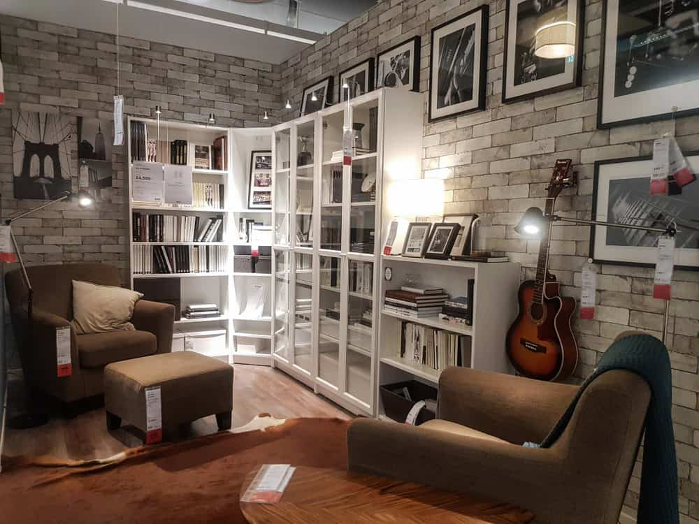 This classic living room design features grey brick walls adorned with framed wall art. The traditional brown sofa seats and ottoman made of soft fabric make for a comfy place. While the walls are dedicated to art and music, the white shelf is stacked full of books. The wooden floor complements the sofas to bring the whole look together.
