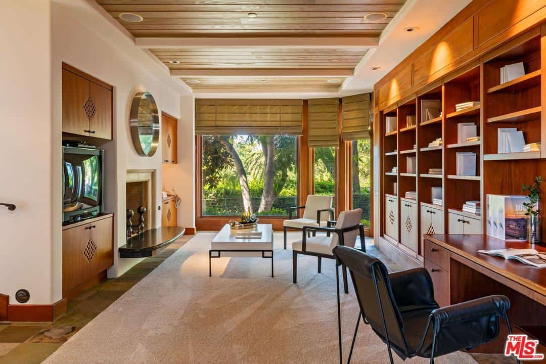 This home office has a mid-century modern style to it with the plain wood desk and mid-century modern style furniture in the sitting area around the fireplace.