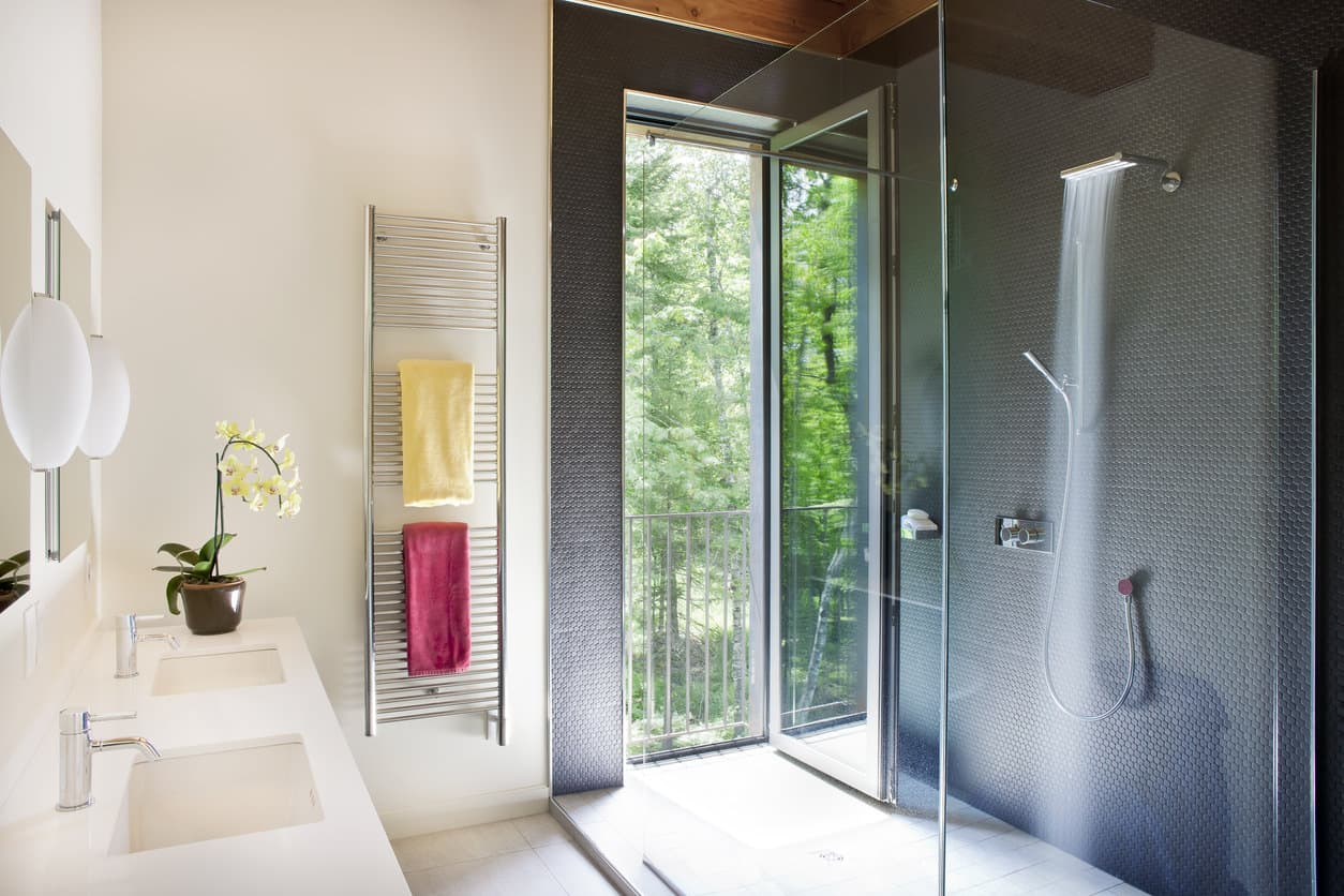 This master bath is crafted in such an intuitive way that a balcony door leads directly into the huge walk in shower lined with a floor to ceiling glass panel. The large rectangular shower head produces a mist that combines with the dark gray miniature hexagonal tiled shower wall seamlessly. A light countertop with chrome fixtures top the look of this modern nature paradise.