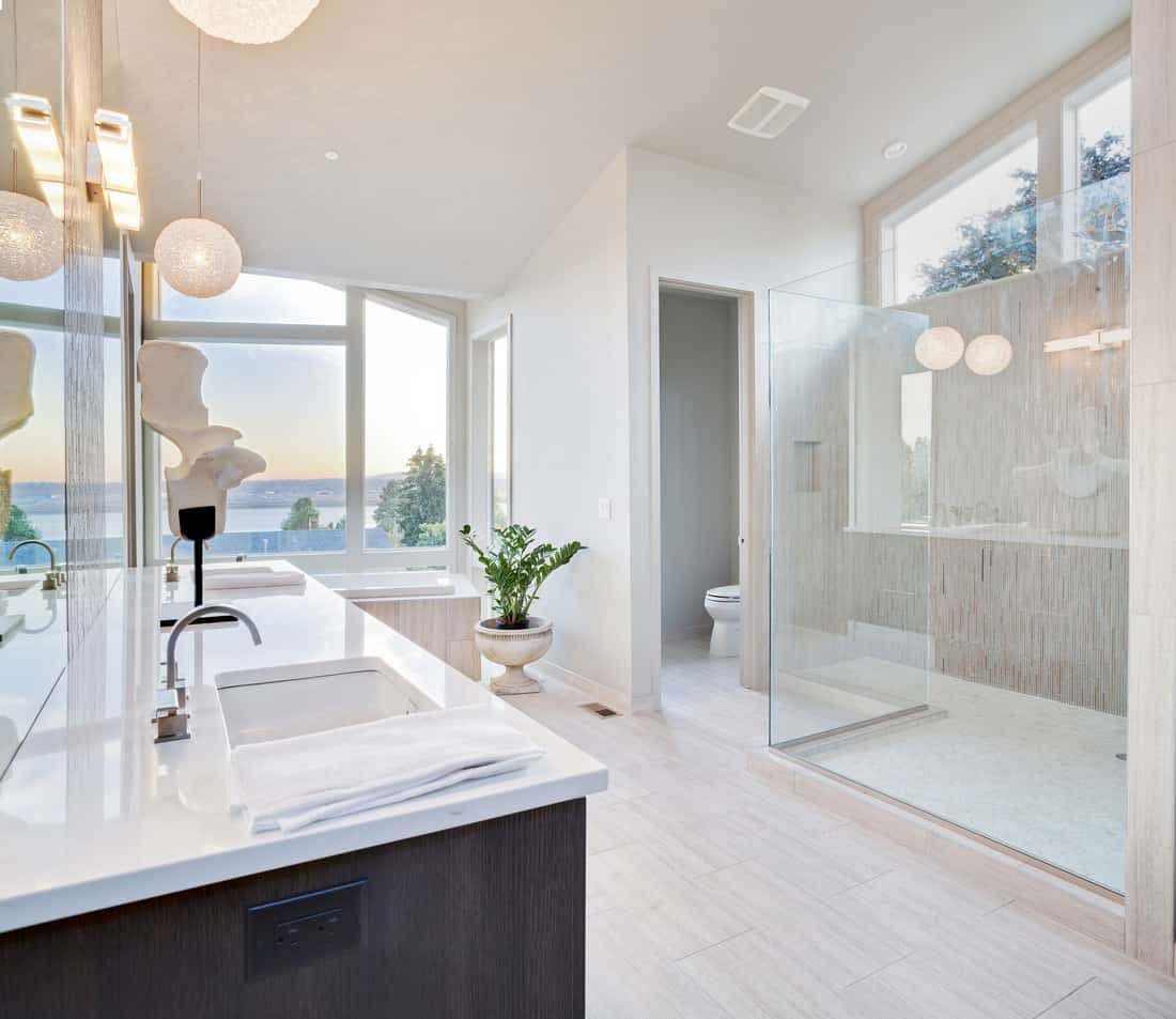 Huge water front windows add a sensational view to this modern master bath and huge walk in shower. Almost all components of this bathroom are white or off white coloring giving the extravagant view a neutralizing balance for a relaxing showering experience.