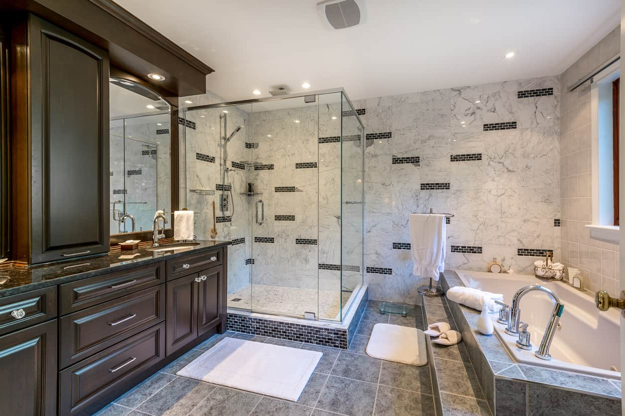 This stunning master bath is lined with dark cherry cabinetry surrounding the vanity and mirror, with a snow like marble pattern lines the big walk in shower. A staggered navy colored brick design adds life to the shower wall and a blue grey middle tone large tile line the floors to pull it all together.