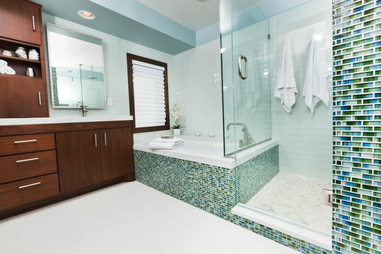 Walls of blue, turquoise, and green hues come together in the form of symmetrical mosaic stacked patterned walls. The garden tub combines seamlessly with the large walk in shower enclosed with clear glass panels. A floor of tan and off white miniature tiles make the shower look like the sand on a beach. This master bath will make you feel like you are on an island paradise getaway.