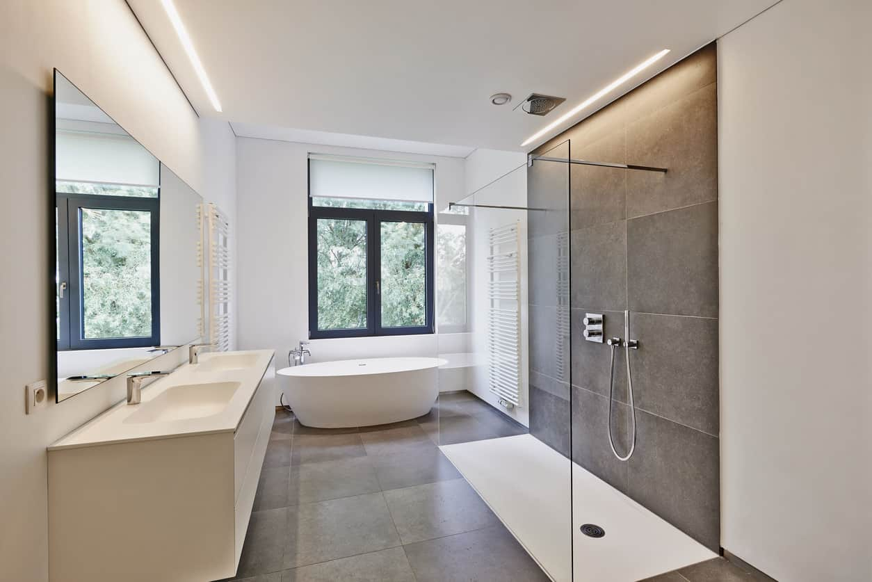 This sleek modern master bathroom features a unique design that camouflages the large walk in shower to where you wouldn't even know it was there. A single wall of crystal clear glass stands in the middle of the room with two chrome bars outstretching from the wall to make it appear invisible. The shower head is intuitively camouflaged and built right into the ceiling and the brown extra large square tiles give the bathroom a darker toned touch.