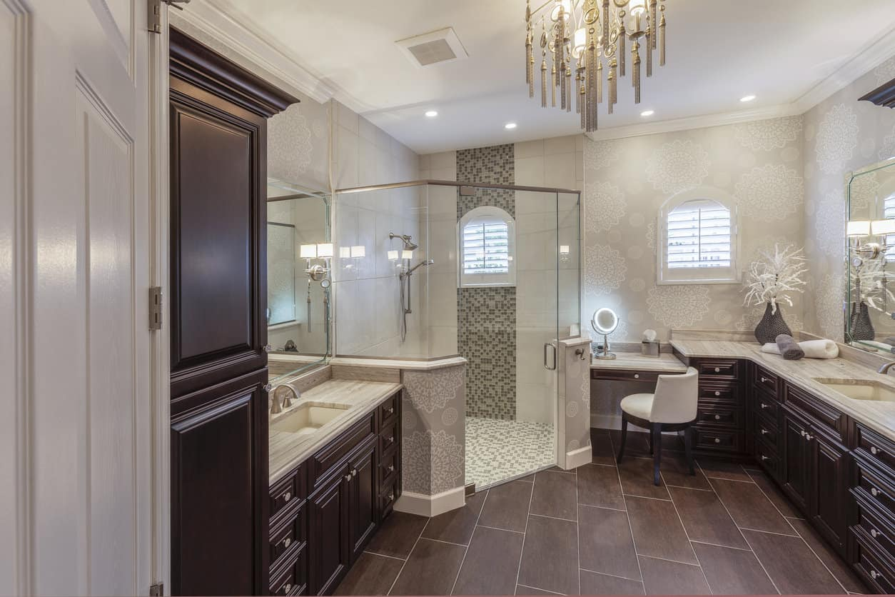 The extremely spacious walk in shower encompasses a corner of this elaborately designed master bath. Mosaic style miniature tiles line the floor and a stripe on the shower wall adding precise detail to the sleek glass paneled shower. Elegantly carved dark cherry cabinets line the walls with a king size marble top vanity and cut out sink.