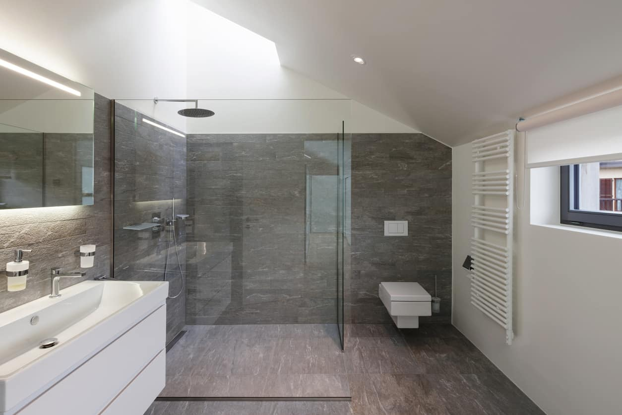 This master bath is as modern as it gets, a wood neat and smooth wood pattern lines the walls in a gray pine color and large single pieces of glass panels enclose giant walk in the shower. The grandiose waterfall style shower head fits in with the modern sharp cut skylight that shines right down into the shower.