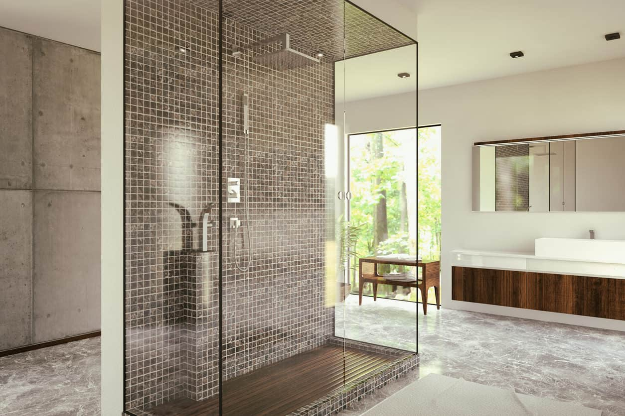 An elongated spacious walk in shower is the epitome of this master bath. Utilizing a half wall in the middle of the room, three walls of glass paneling enclose the mini mosaic tiled fourth wall and one of a kind dark pine wood shower flooring. A dark pine single element wall mounted vanity combines with a solid off white countertop and basin style sink to add finishing touches.