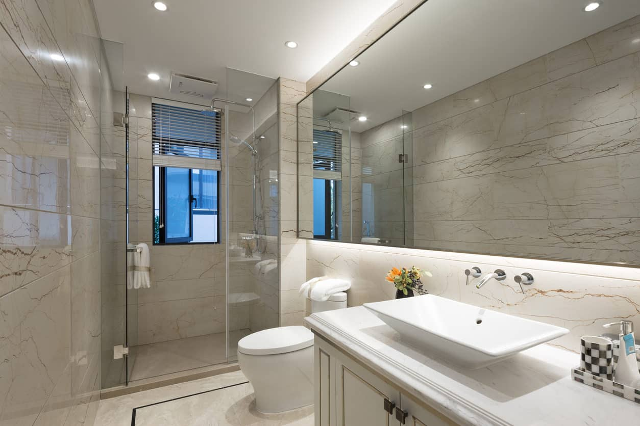 Shiny golden accented white marble tiles line the walls and flooring of this long inlet shaped master bath. The spacious walk in shower features glass paneling to finish off the enclosure of the surrounding polished three walls. The double fountain style shower head and built in towel brackets make for a modern look that compliments the wall length mirror with built in underlighting.