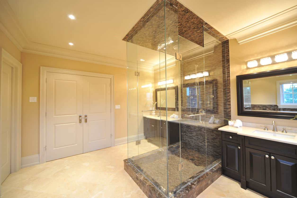 This elegant master bath is lined with detailed crown molding and two huge sophisticated but modern style vanity sinks that are separated by the walk in shower. With three walls of the shower made only of glass panels, and sophisticated granite flooring and fourth wall will make you feel like you are showering in the white house.