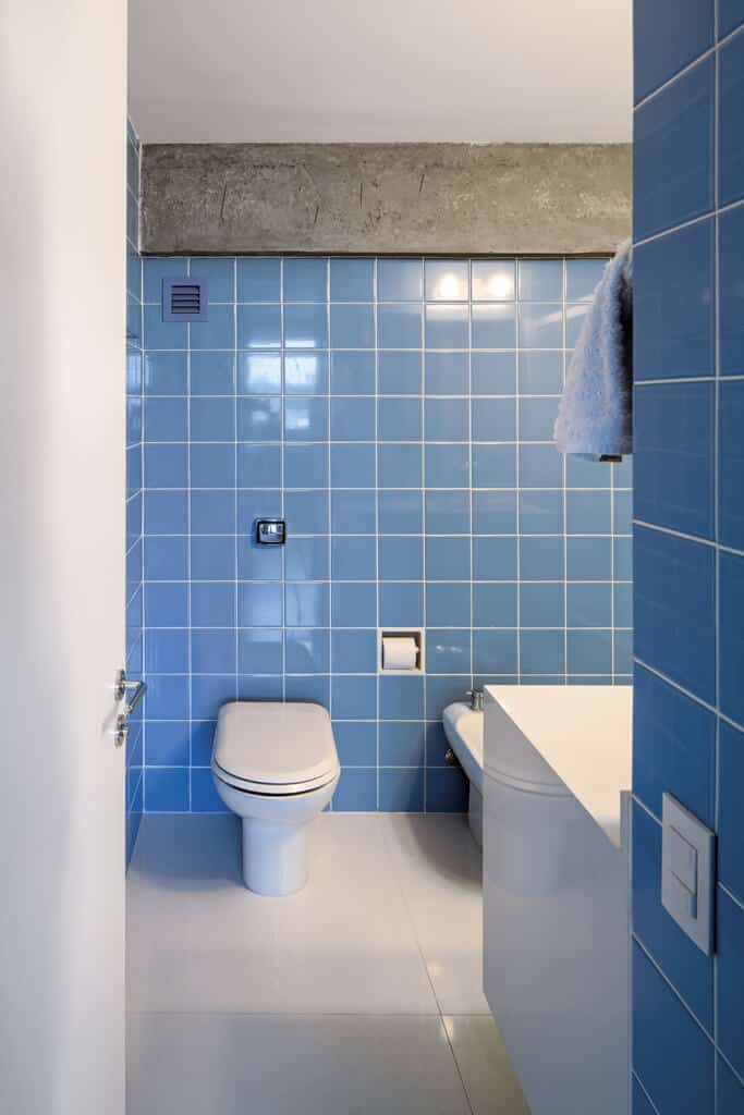 Simplicity speaks for itself and this bathroom with blue-tiled walls and simple flooring does so in spades. The room is free from clutter and is made of clean lines, but the lovely blue colors of the walls balance what would have been a stark room.