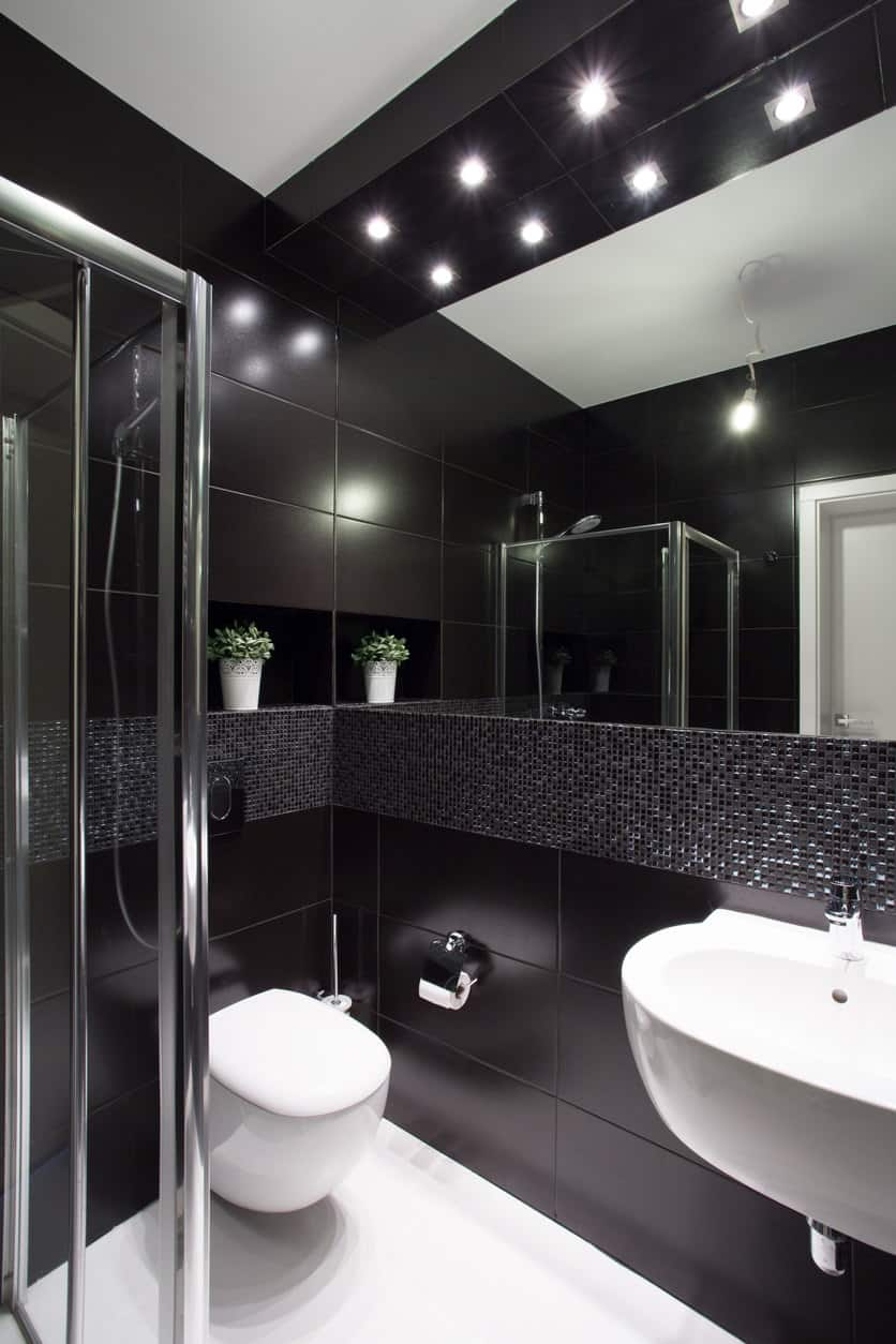 With its black and white glimmer and shine on the walls and overhead lights that give the appearance of spot lots on a stage, this room definitely has that Hollywood glam feel. It has a tank-less toilet to save on space. There is also a ledge on one wall that is perfect to hold accessories.