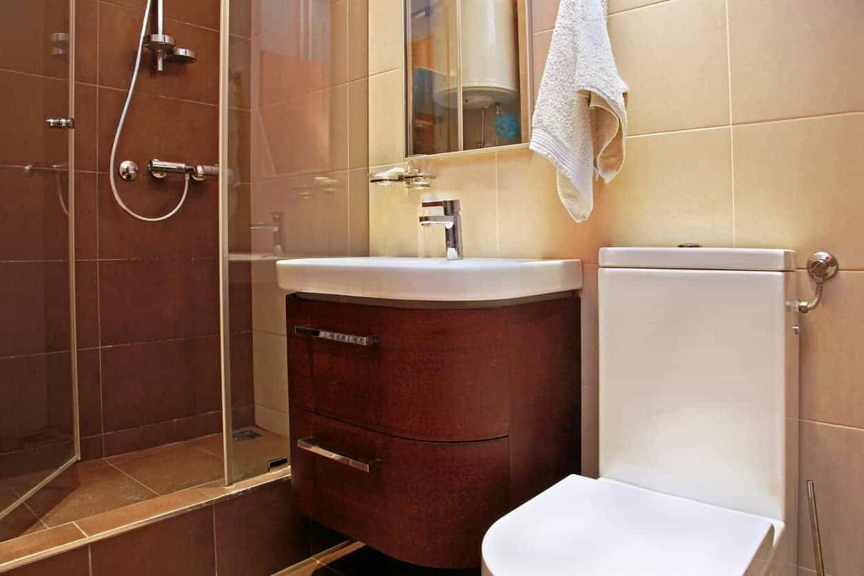 This bathroom has a unique flair to it with its step-up shower stall that makes the room feel as if it has two sections. The toilet has a slender tank which gives the room more space. It also has a rounded vanity with drawers for added storage.
