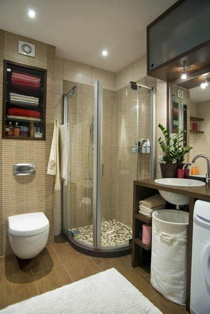 This room utilizes height to distract from its small size. By having cabinets and storage at a higher level, it draws the eyes upward. This gives the appearance that the room is bigger than it is. From its mosaic tile shower floor and colored accessories, the room provides comfort and warmth.