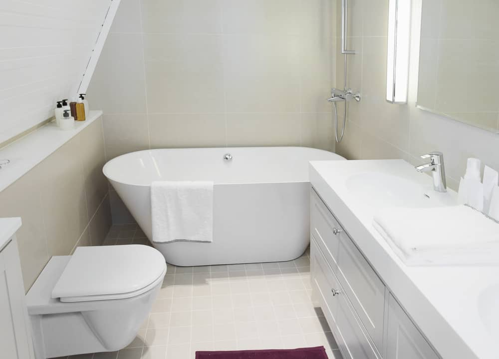 This small bathroom has a tank-less toilet, an extra deep bathtub, and long vanity all dressed in white. Very simple yet elegant at the same time with its cream-colored walls and tiled flooring.
