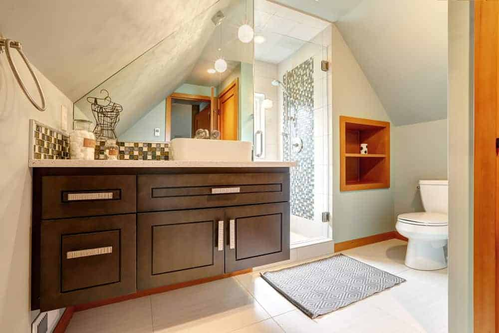 This bathroom ties together various elements of interest. From its dark wood vanity that floats above the floor, and its storage and door stained a rich gold, to its angled vanity mirror and roof. The shower is situated in such a way that it appears as if it is a completely different room.