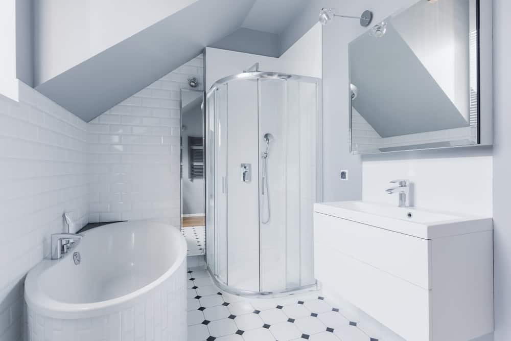 The all-white walls, tiles, and fixtures are offset by the chrome faucets and trim. An oversized mirror hangs over a trough style sink. There is a uniquely cornered shower that saves space in the rest of the room. This room is not only efficient in its space-saving set-up but attractive as well.