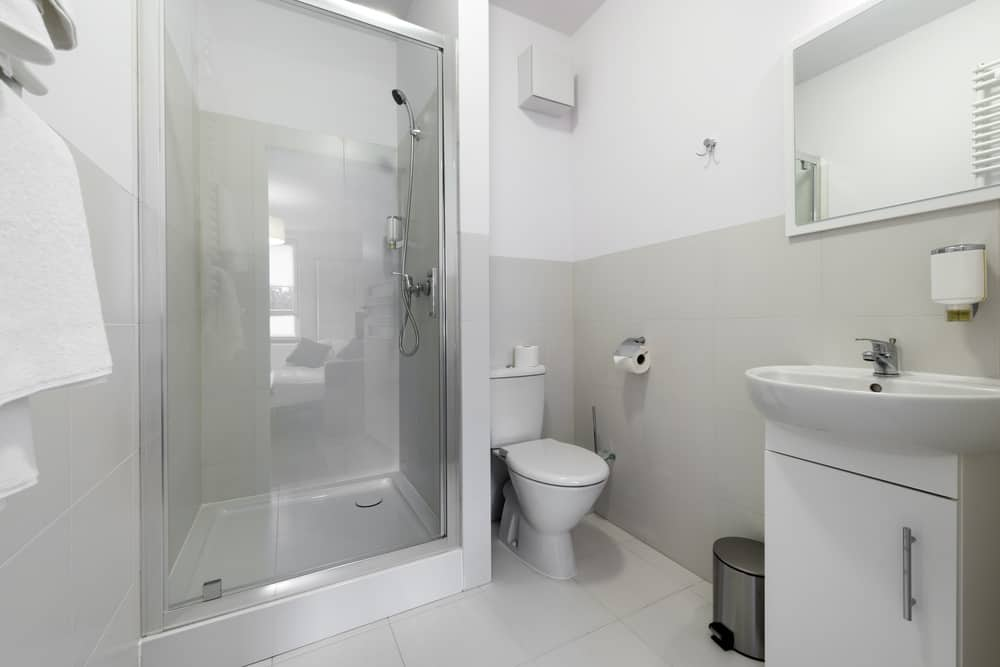 This nearly all-white bathroom has a touch of gray which ties together with the rest of the room. By omitting a bathtub and utilizing a shower equipped with a clear glass shower door, the bathroom is given more needed space. It also has a larger than normal vanity mirror which gives the illusion of a larger area.