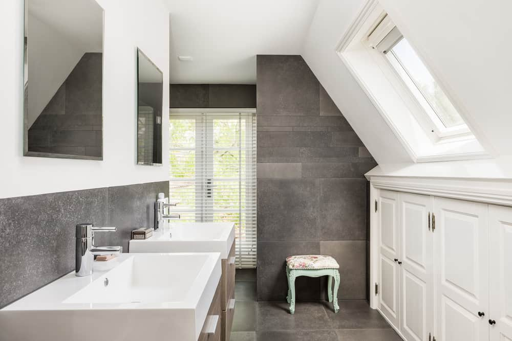 This bathroom provides double sinks and vanities in a modern style of clean and crisp edges of white. An angled window offers a unique view of the outdoors and is placed over an abundance of storage area. The gray-speckled backsplash is a compliment to the gray slate-style walls and floors.