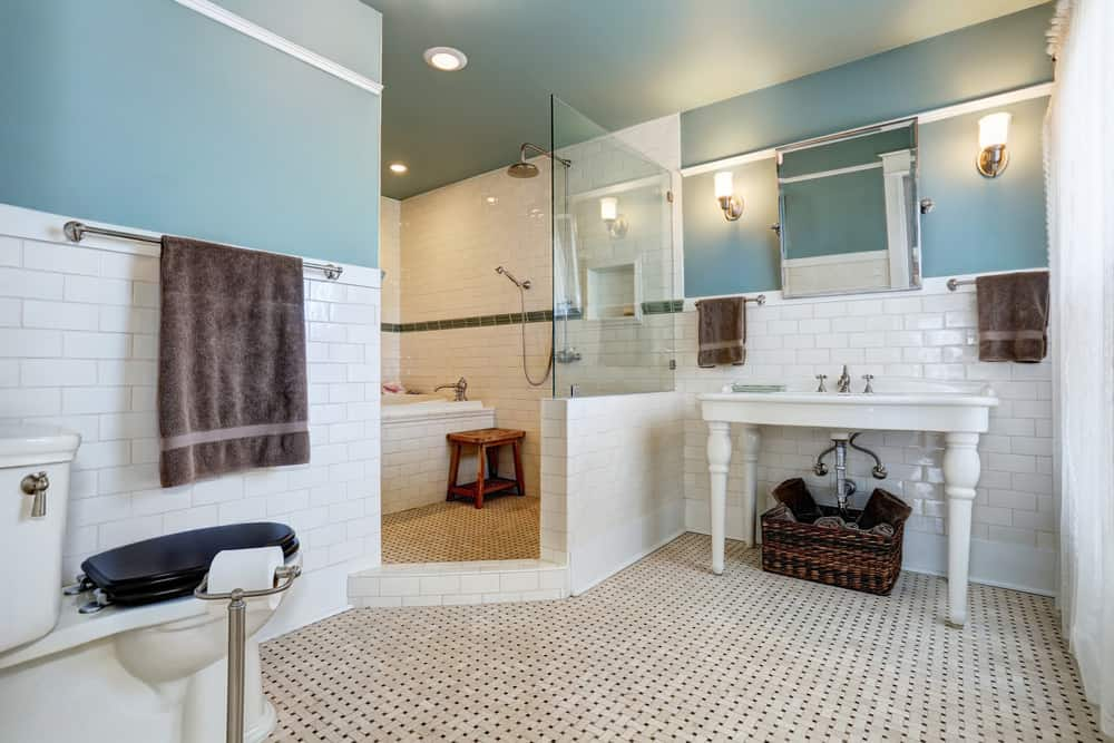 This bathroom is a blend of the old and modern, urban and rustic. The room has beautiful pale blue walls, white tiling and dark blue toilet cover, which is in stark contrast to the wooden step stool next to the bathroom and a wicker basket below the sink.