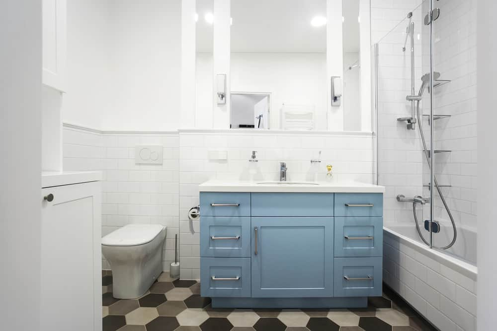 The pristine white walls, fixtures and glass surfaces of the bathroom are tempered by the black, grey and white honeycomb tiles of the floor. The monochromatic colors make the powder blue vanity pop out even more.