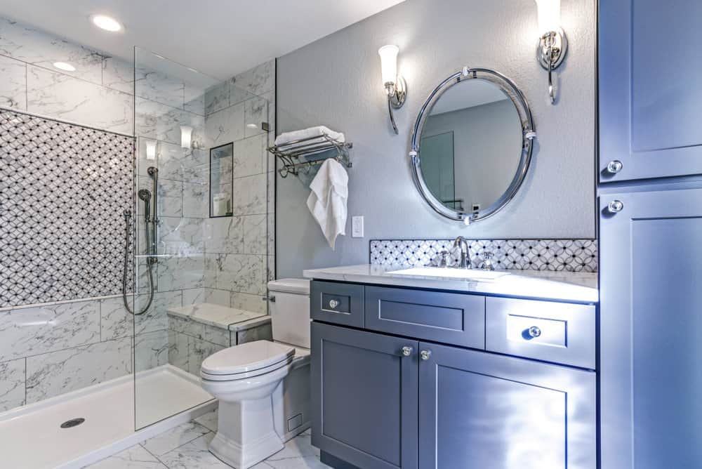 This beautiful bathroom is not that huge with regards to its size, but the clever use of a mirror and glass makes it seem so much more spacious. The white and grey marble walls and flooring, the white fixtures and the round mirror, bracketed with two lamps, makes this room look like it's incased in a bubble.