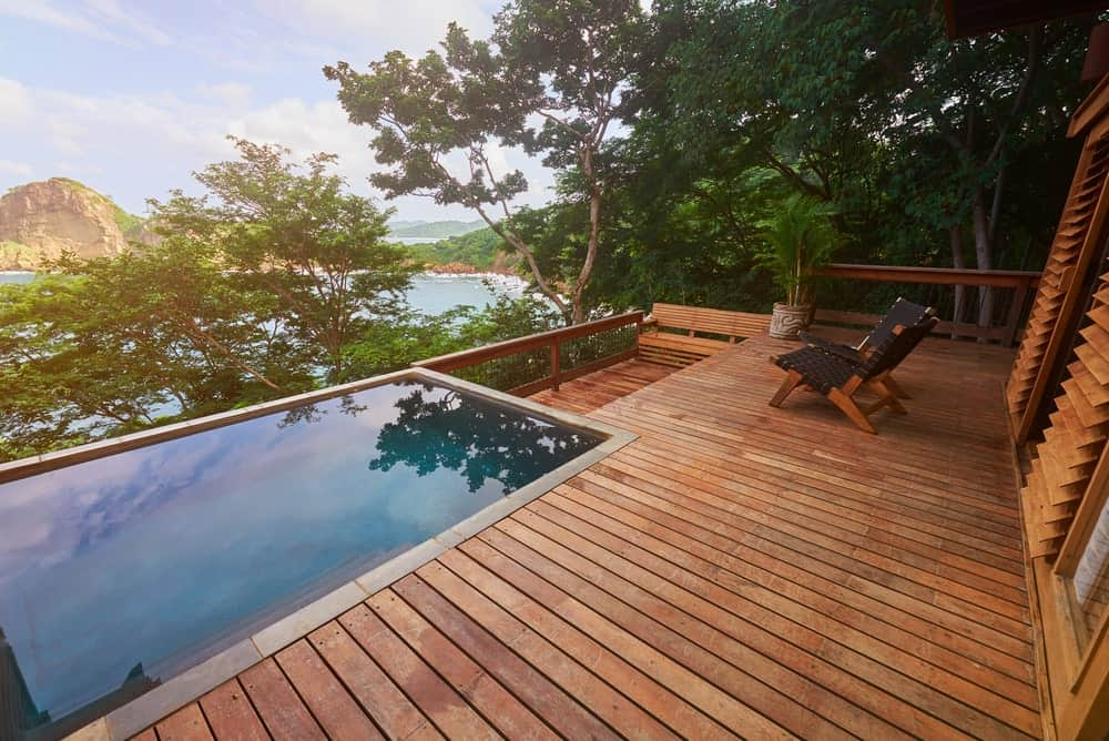 Deck with infinity pool surrounded by trees.