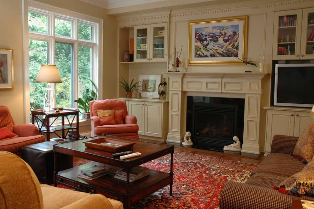 The pink armchairs and the red Persian rug gives this Georgian Colonial Style family room an air of vibrancy