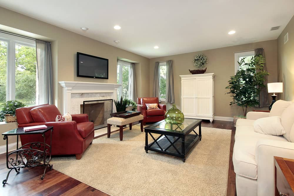 The dark red leather armchairs and the rich brown wood floor are bright accents to this otherwise pale living room