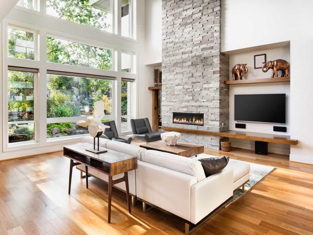 В гостиной с кирпичным камином есть светло-серый кирпичный камин и окна от пола до потолка.