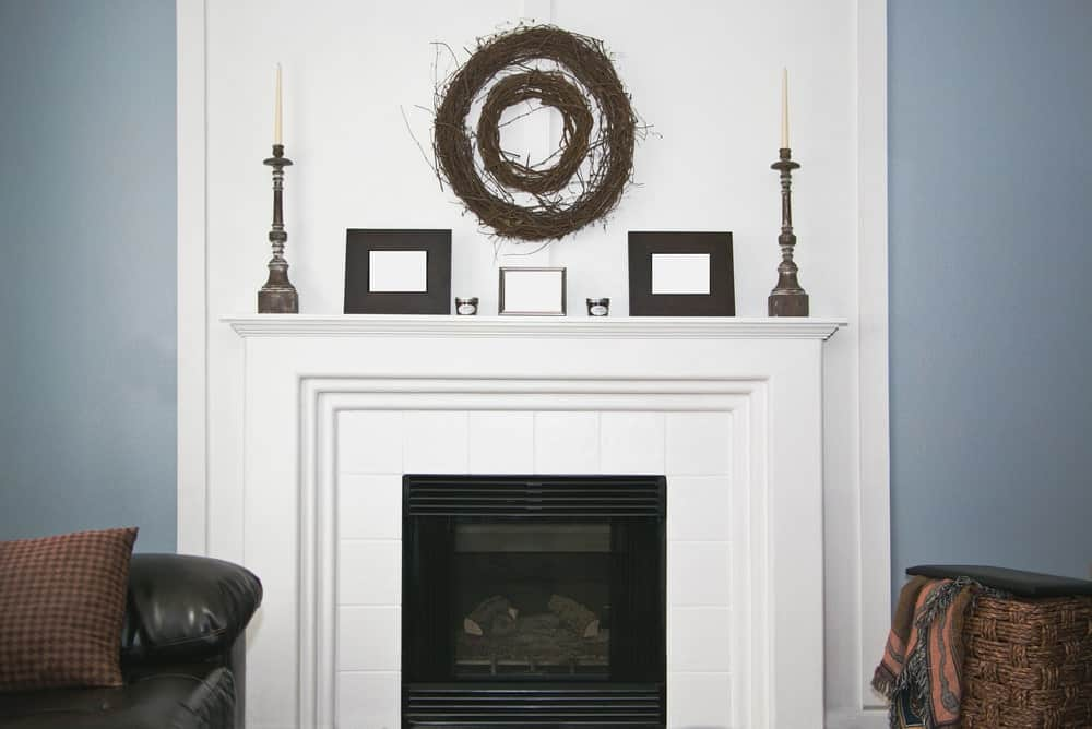 White fireplace with decorative items on mantel shelf.