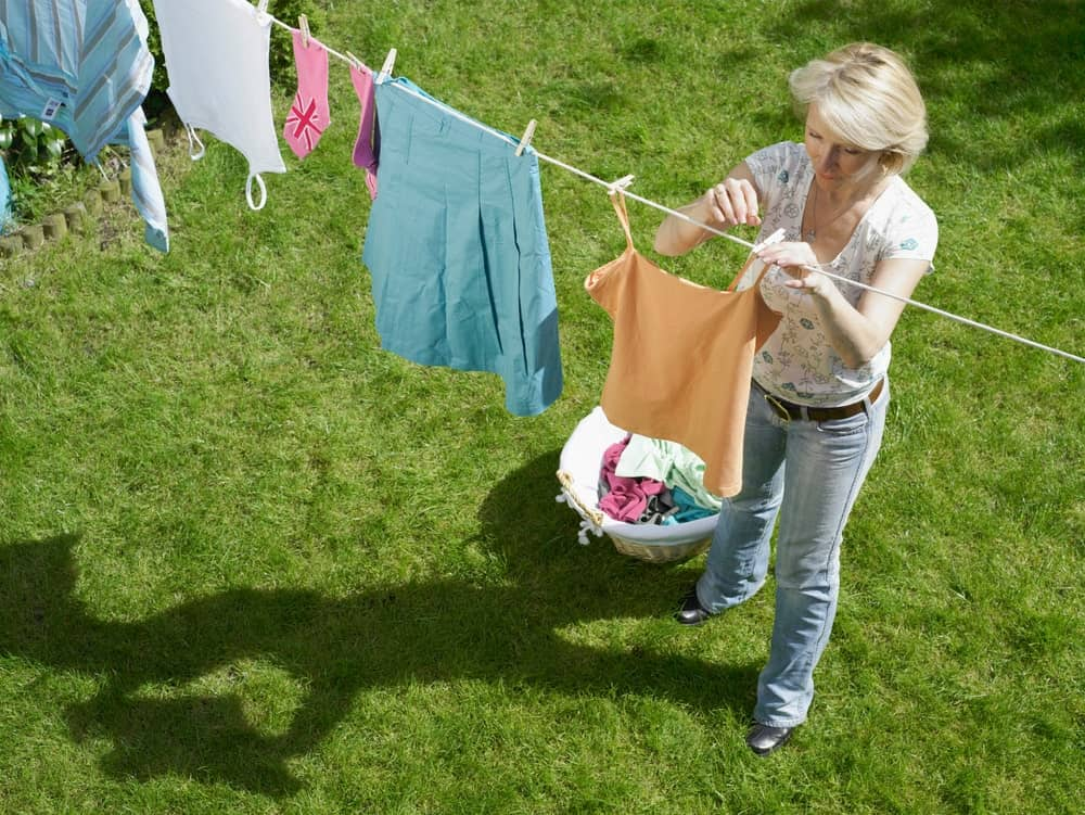 Hanging clean laundry on the clothesline to dry.