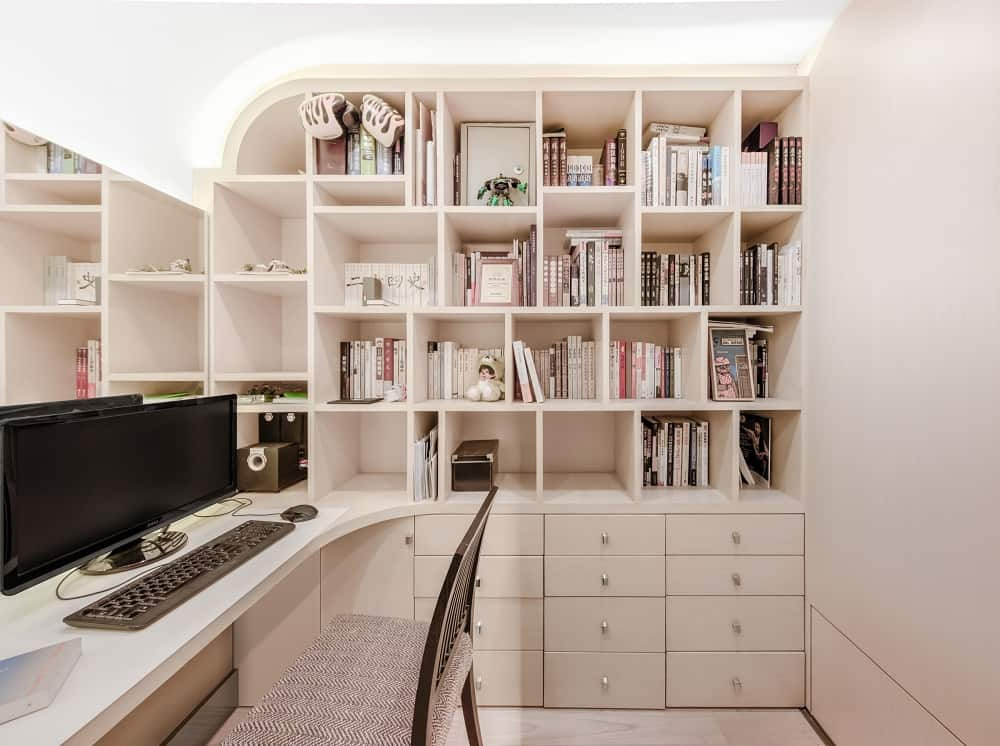 This home office has a consistent beige tone to its walls and built-in shelves with drawers on the side of the built-in desk topped with a mirrored wall.